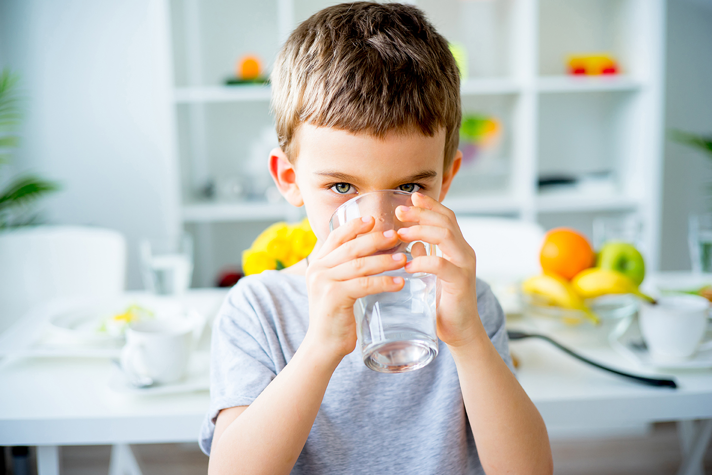 young child drinking water in his kitchen